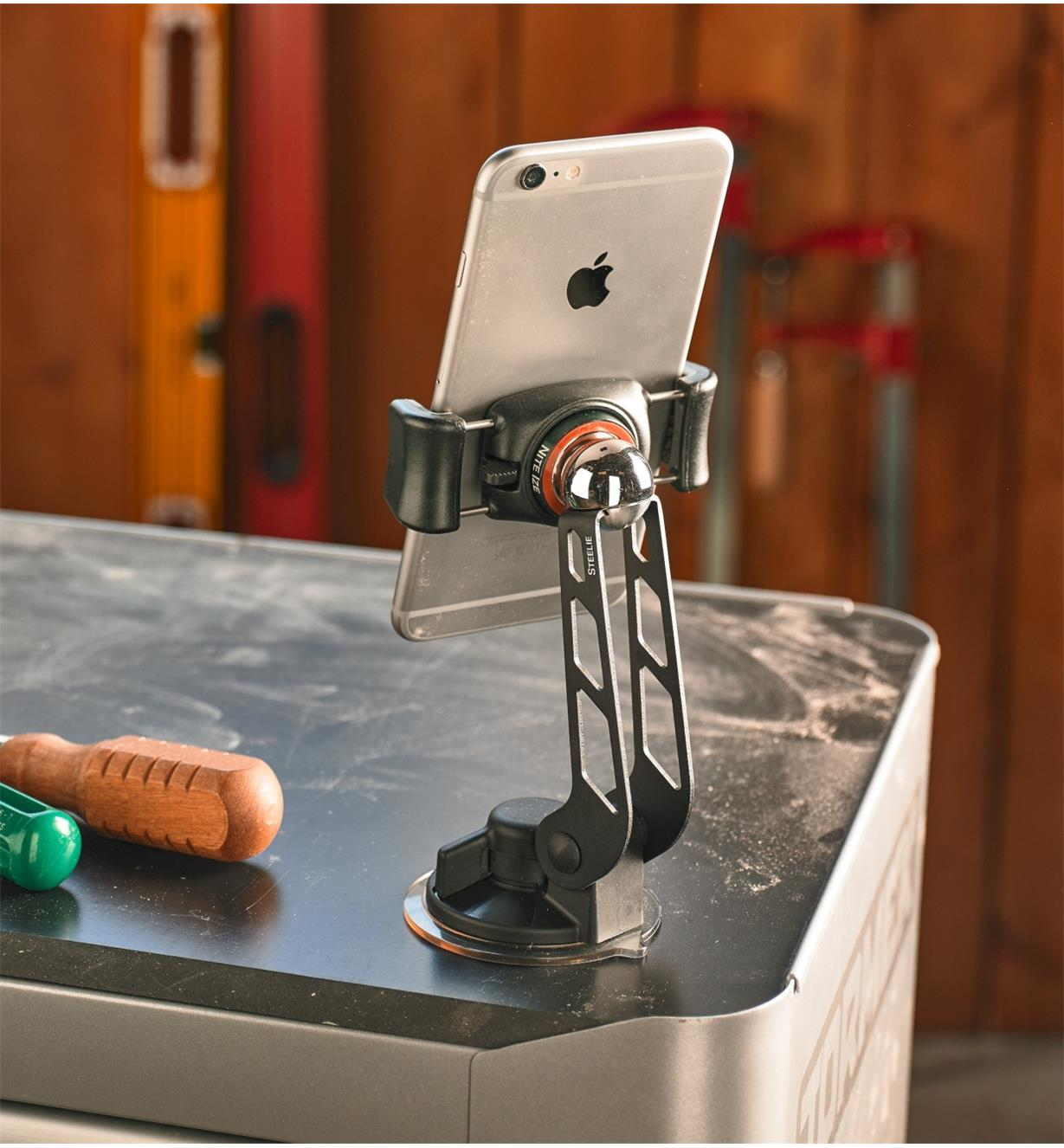 A phone mounted to a work surface using the Steelie FreeMount Kit