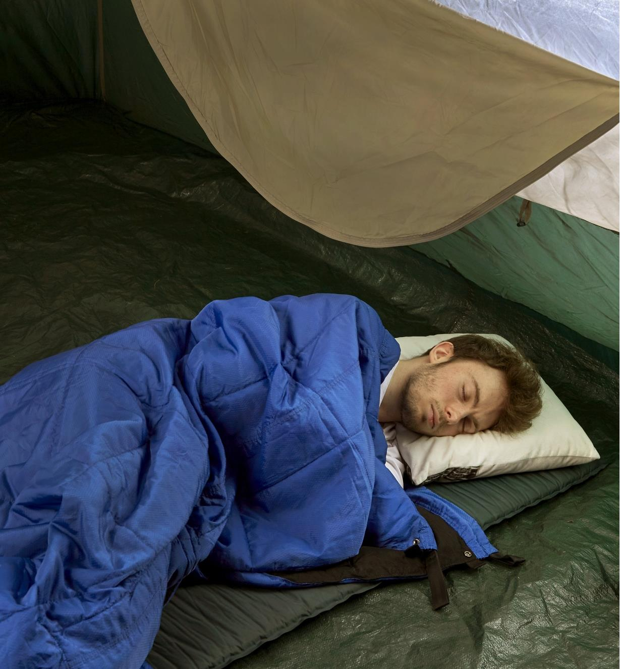 A Kubie multifunction blanket being used as a sleeping bag