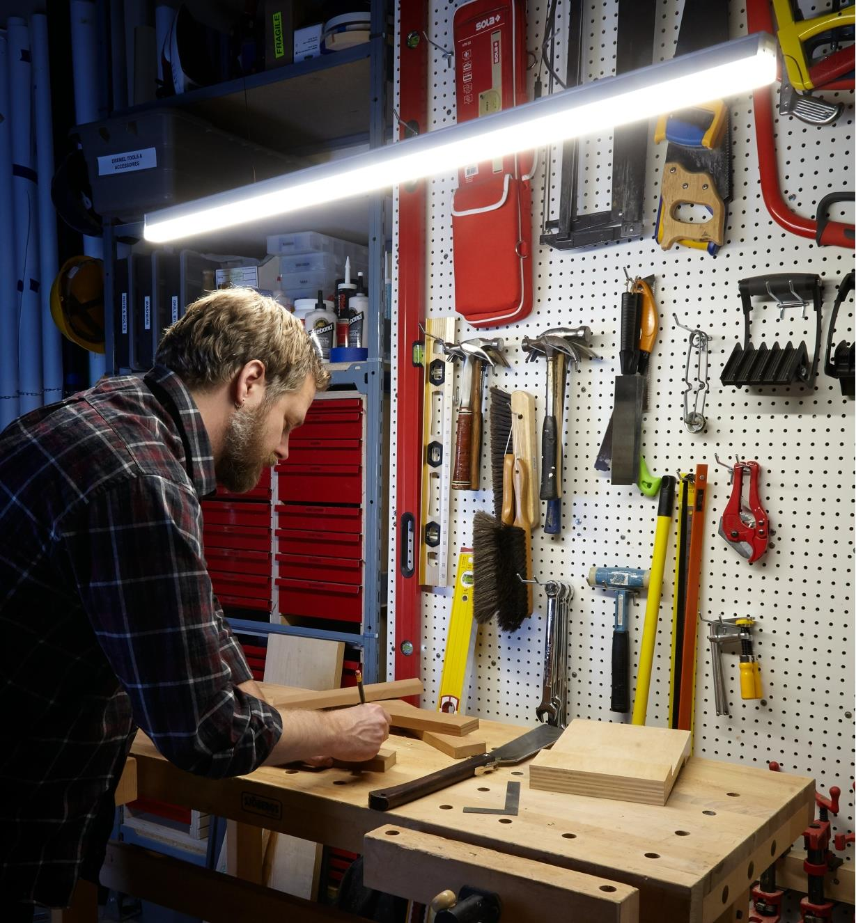 Marking wooden stock on a workbench lit by a SlimLight LED fixture