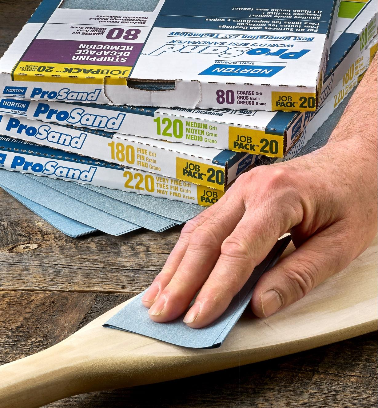 A woodworker sands a wooden canoe paddle with a sheet of Norton ProSand 3X Sandpaper