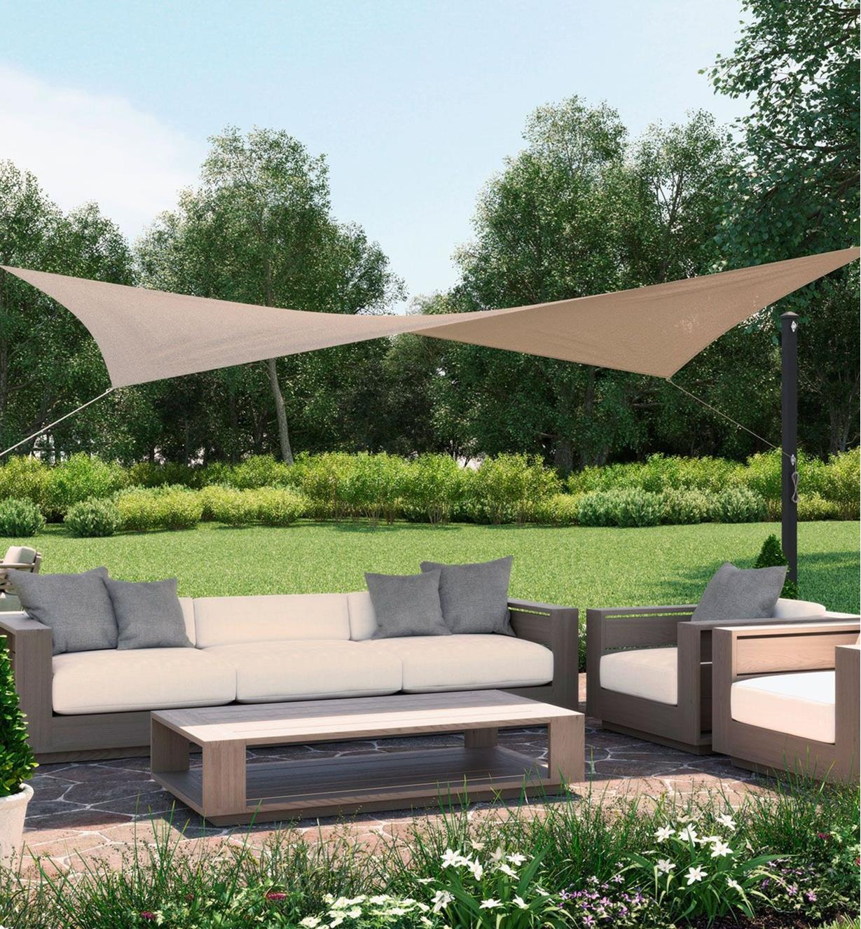 A square shade sail shades a patio seating area