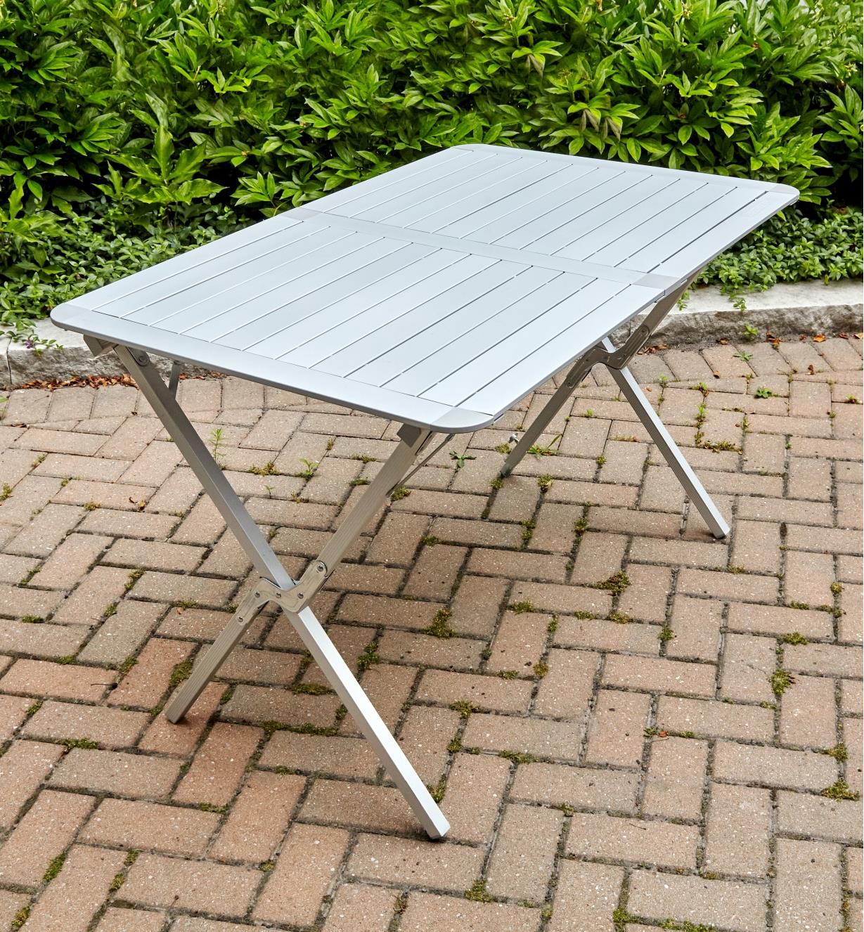 A folding aluminum table shown standing on an interlocking brick patio