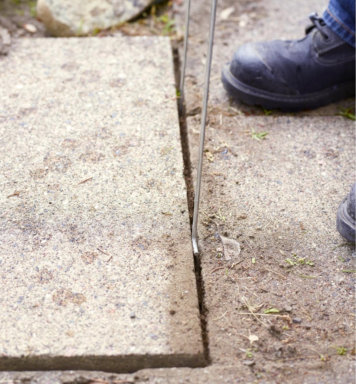 Gros plan du bout de deux crochets de levage SlabSetters glissés entre deux dalles rapprochées