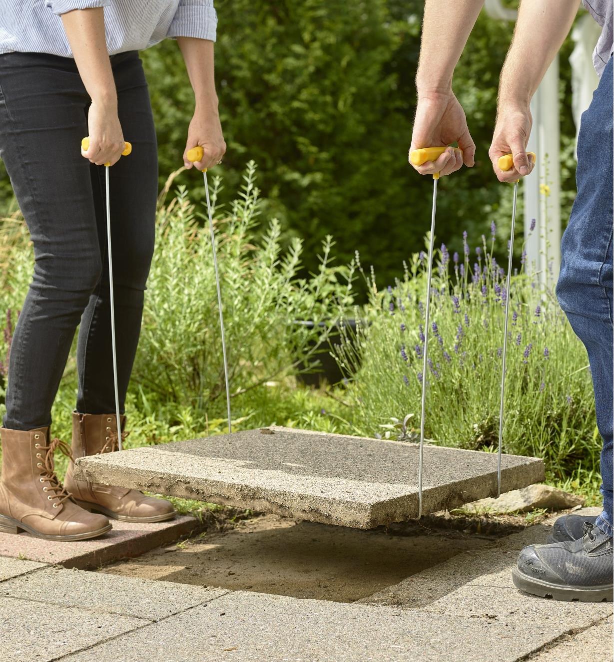 Homme et femme déplaçant une grosse dalle à l'aide de quatre crochets de levage SlabSetters