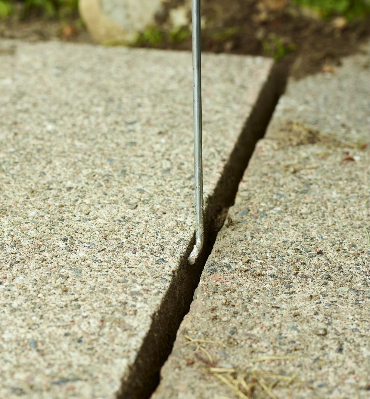 A close view of a SlabSetter tip being slipped between two close-fitting patio stones