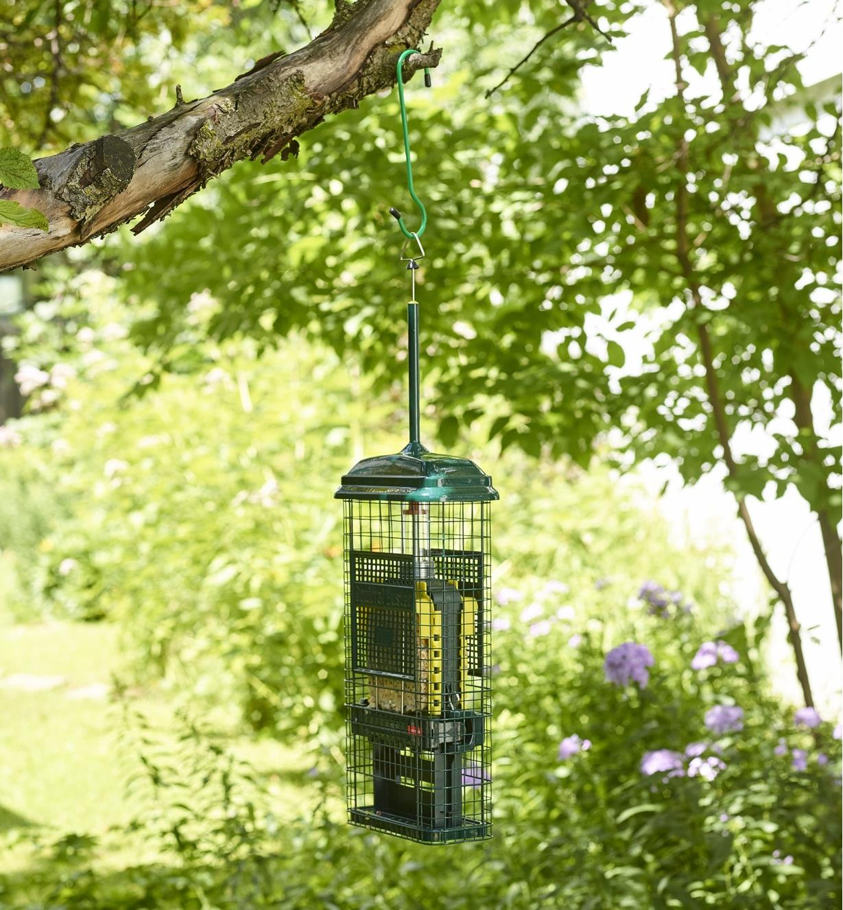 The Squirrel Buster suet feeder hung in a back yard