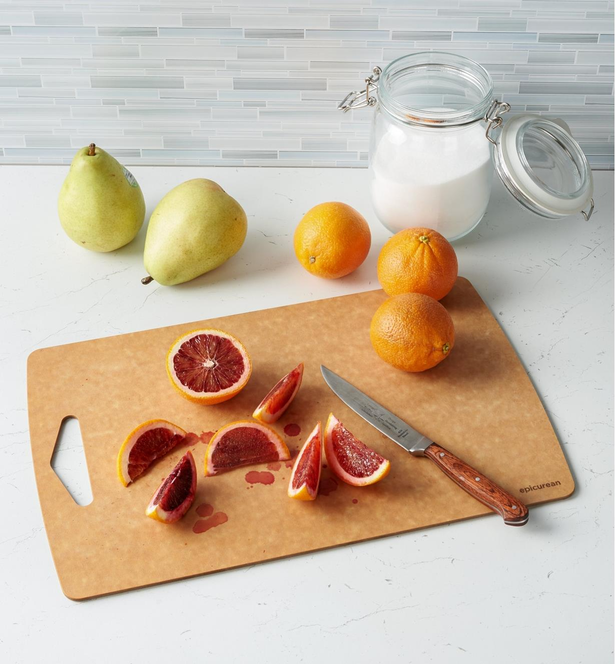 A knife and a sliced orange on a Large Epicurean Prep Series Cutting Board