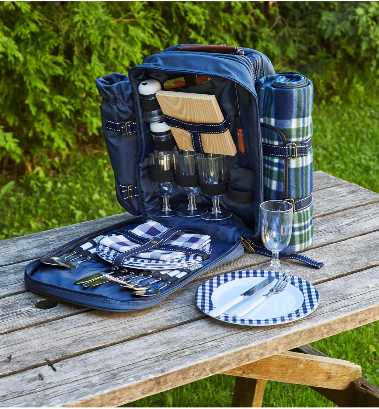 An open Deluxe Picnic Backpack sitting on a picnic table