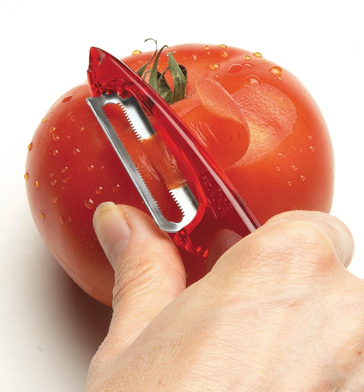 Serrated peeler used to peel a tomato