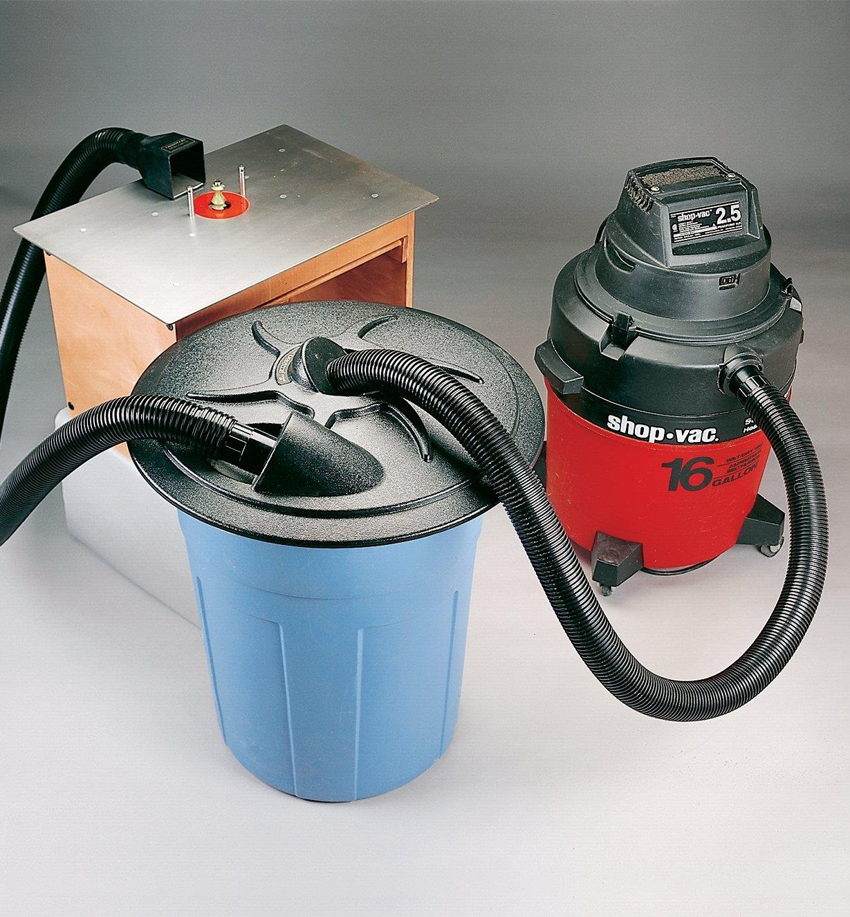 Cyclone lid on a garbage pail connected by hoses between a router table and a shop vac