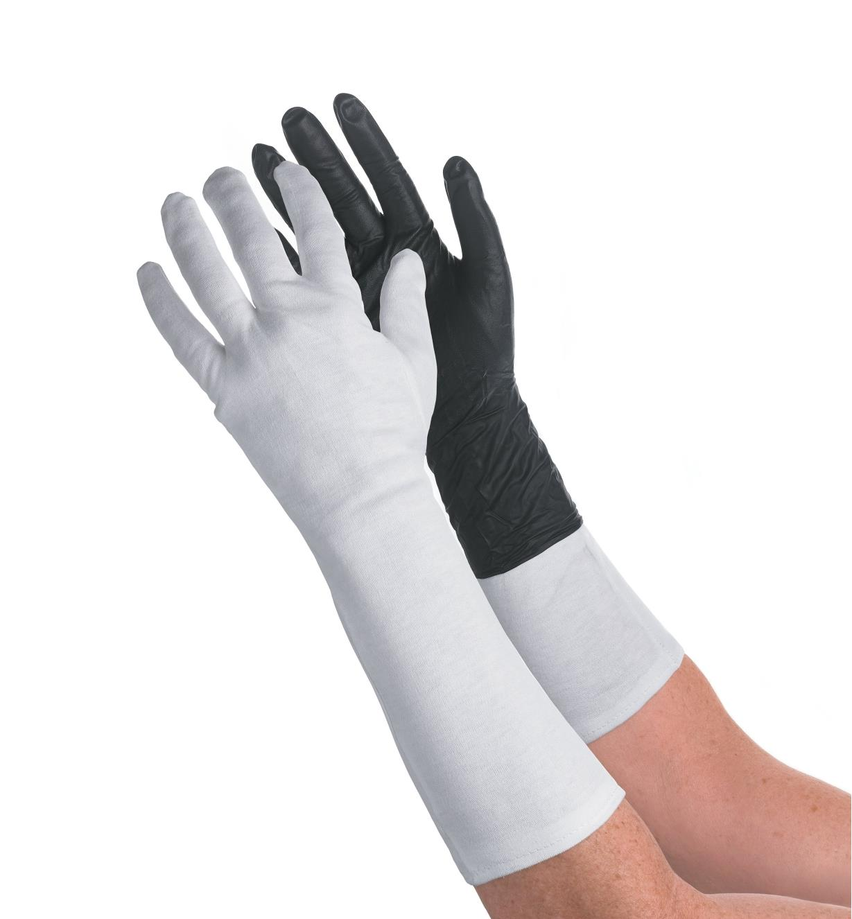 A pair of arms, one wearing a glove liner and the other wearing a glove liner under a glove
