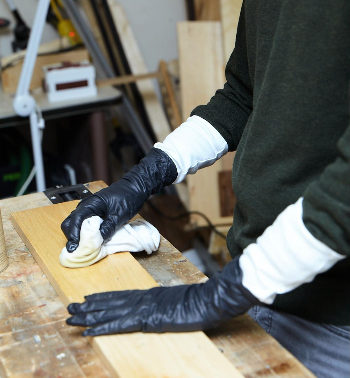 A woodworker wearing glove liners under nitrile gloves while staining a board