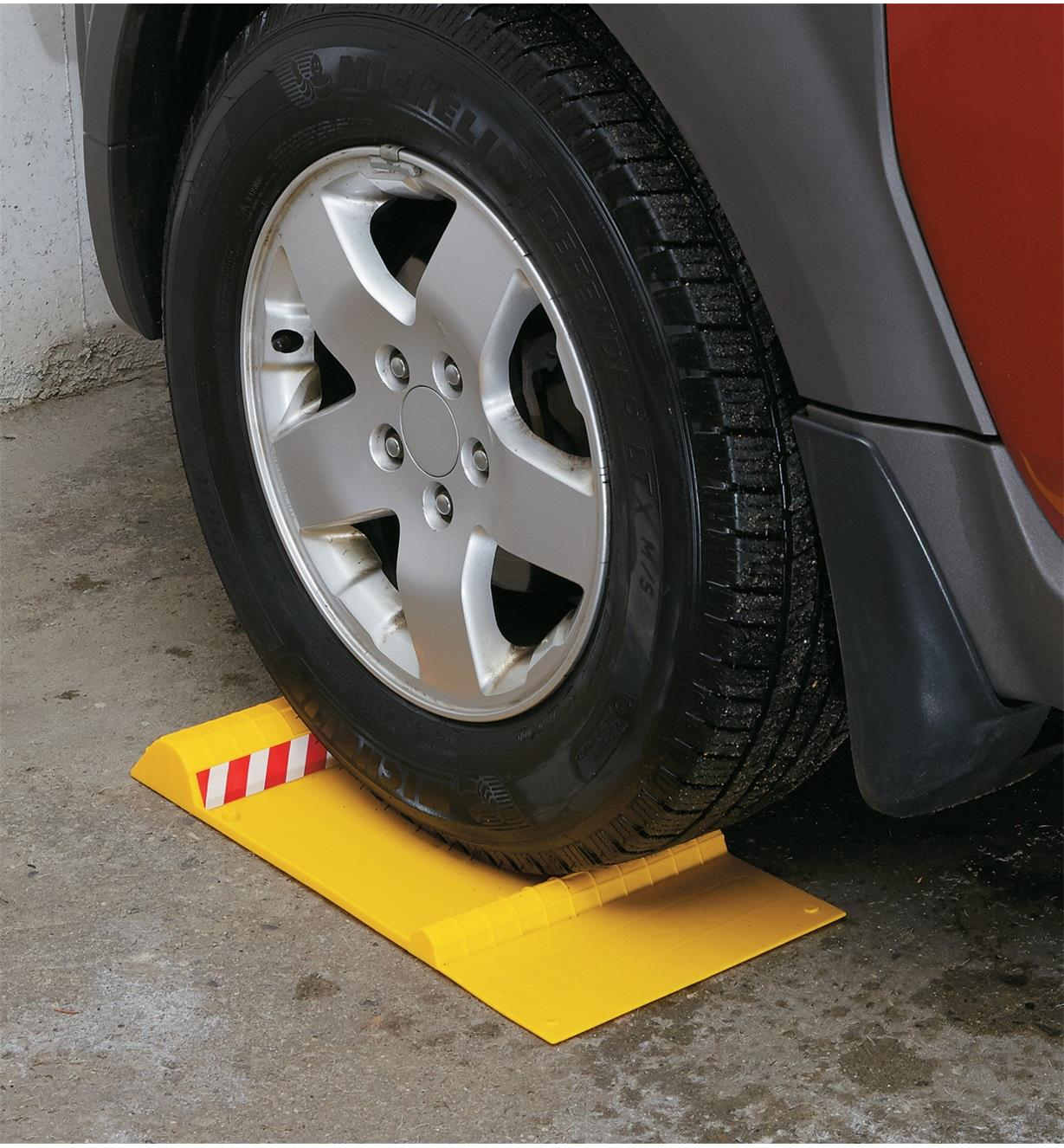 Car wheel positioned on a parking mat