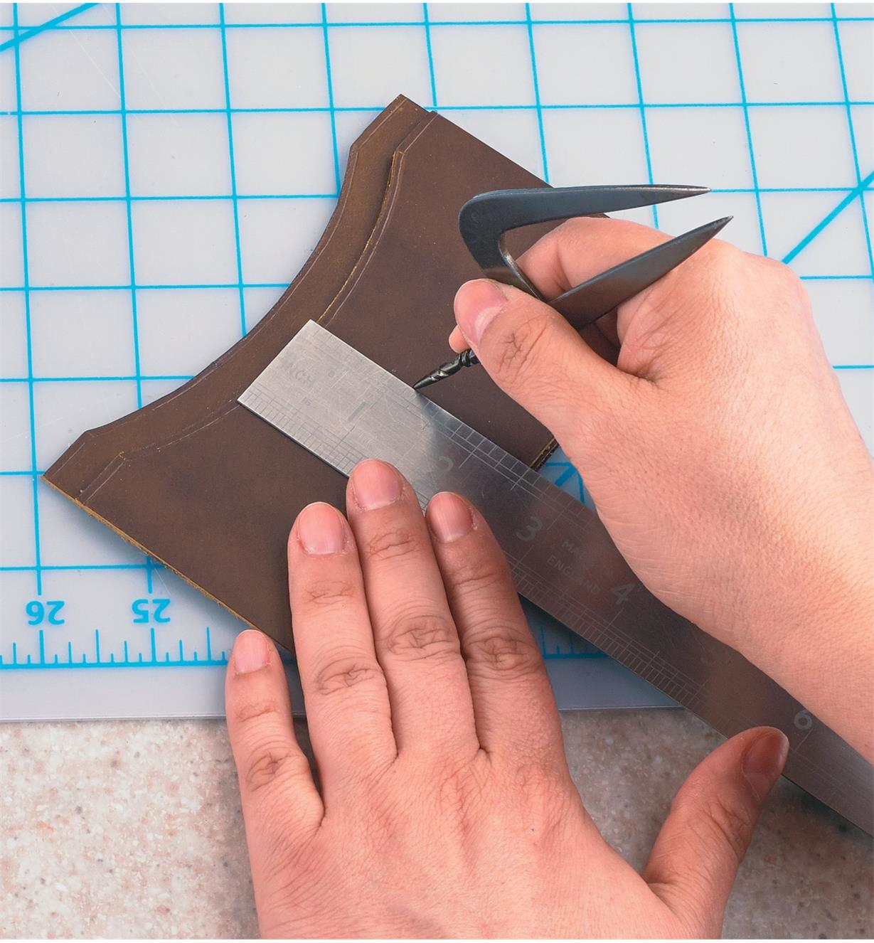 Using the awl point to mark a line on a leather wallet