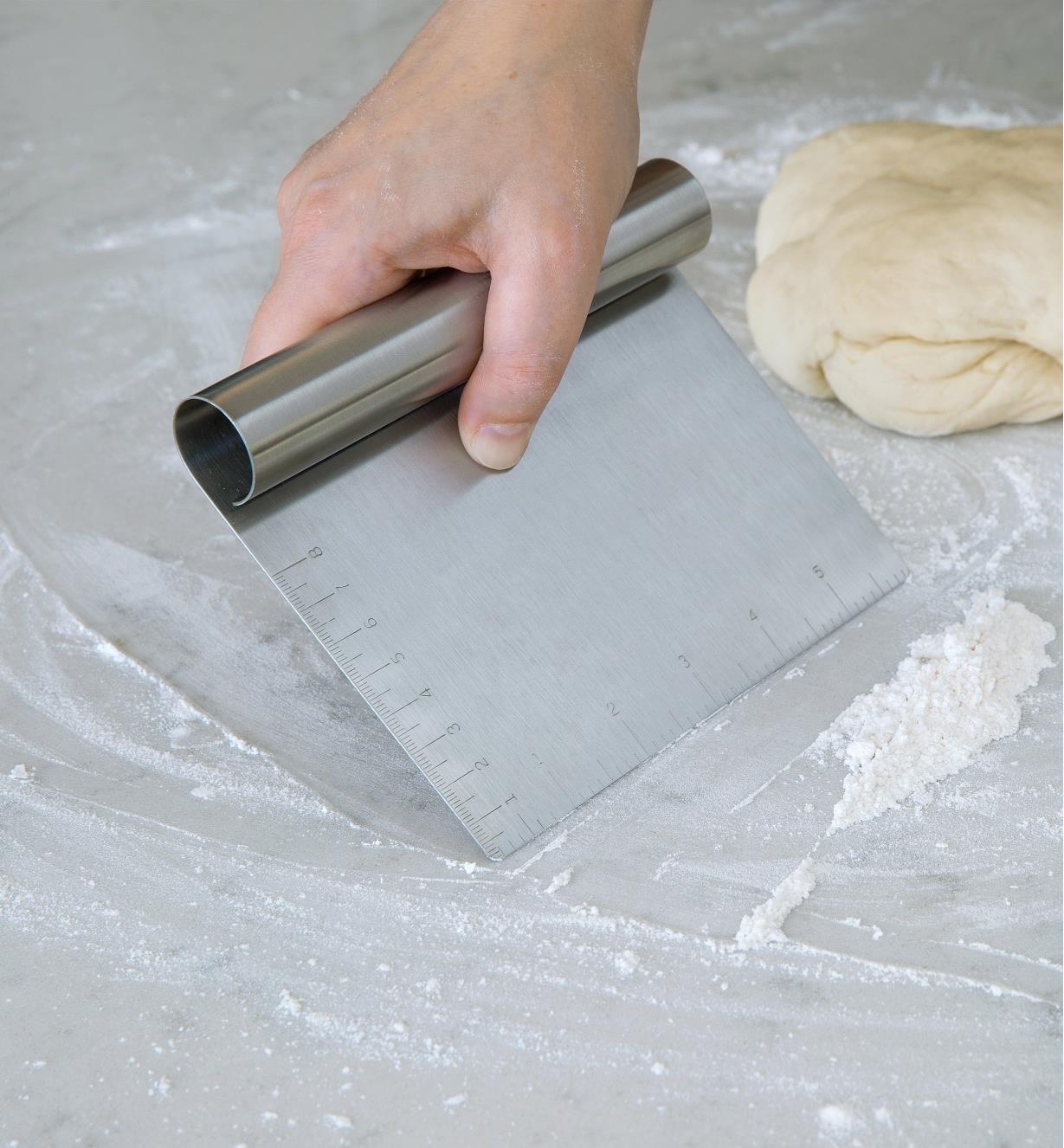 Personne raclant de la farine sur un comptoir avec un racloir à pâte