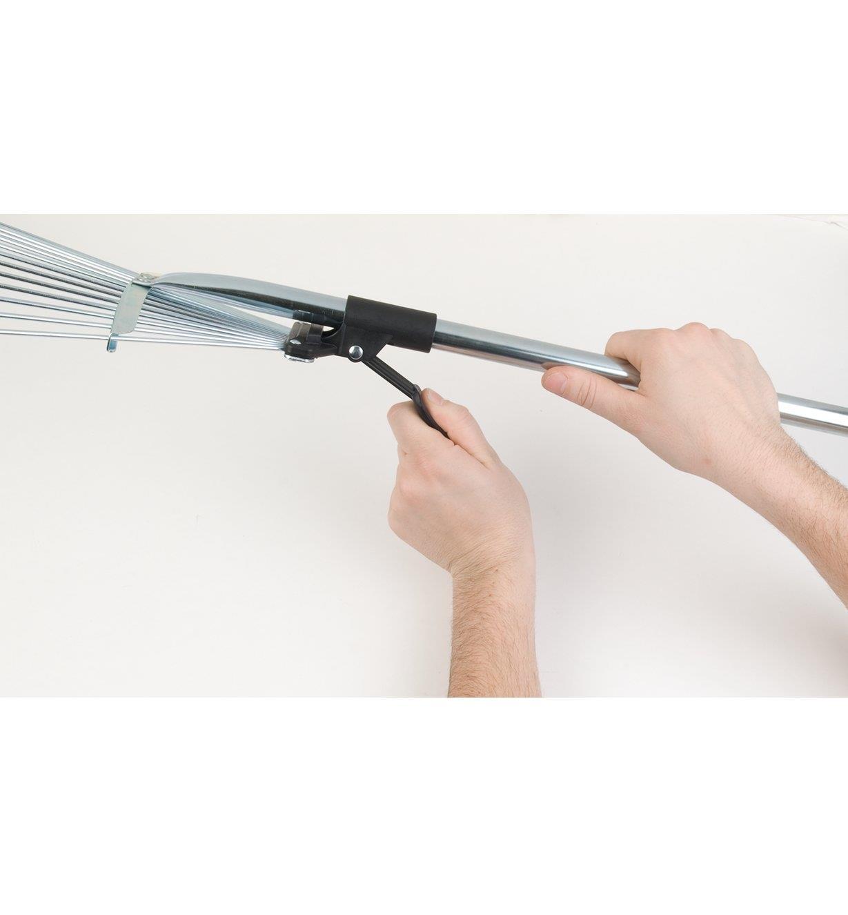 Soulevez le levier du balai à manche long pour régler la longueur du manche et l'écartement des dents.