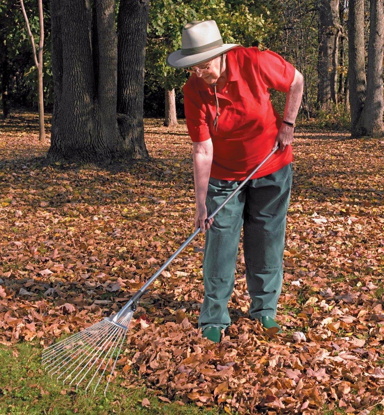 A woman rakes leaves using the Long-Handled Rake
