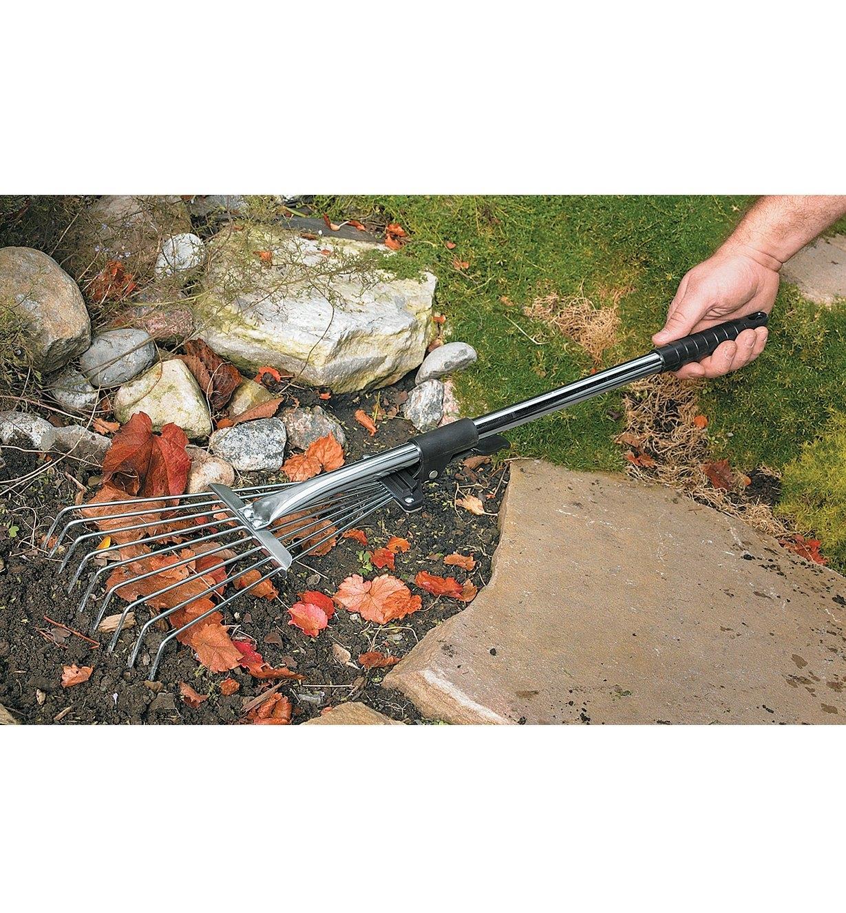 Balai à feuilles à manche court utilisé pour ratisser des feuilles autour de roches dans un jardin