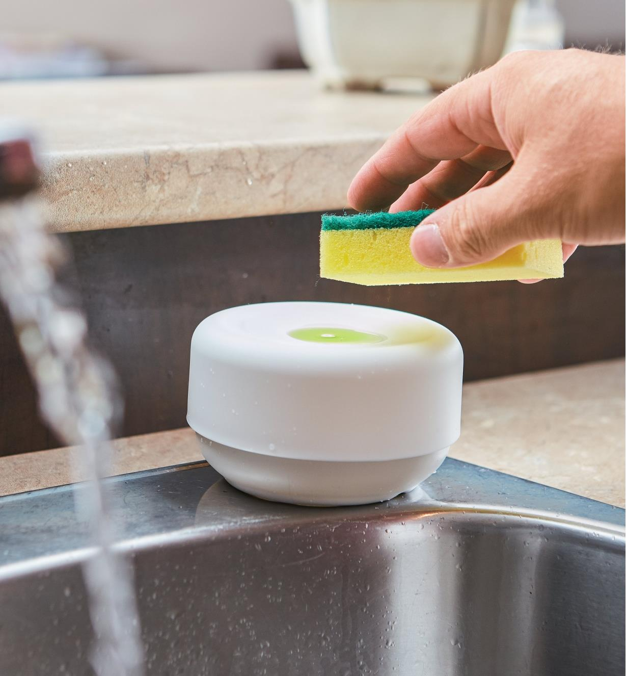 Using a sponge to gather soap from the well on the top of the dispenser