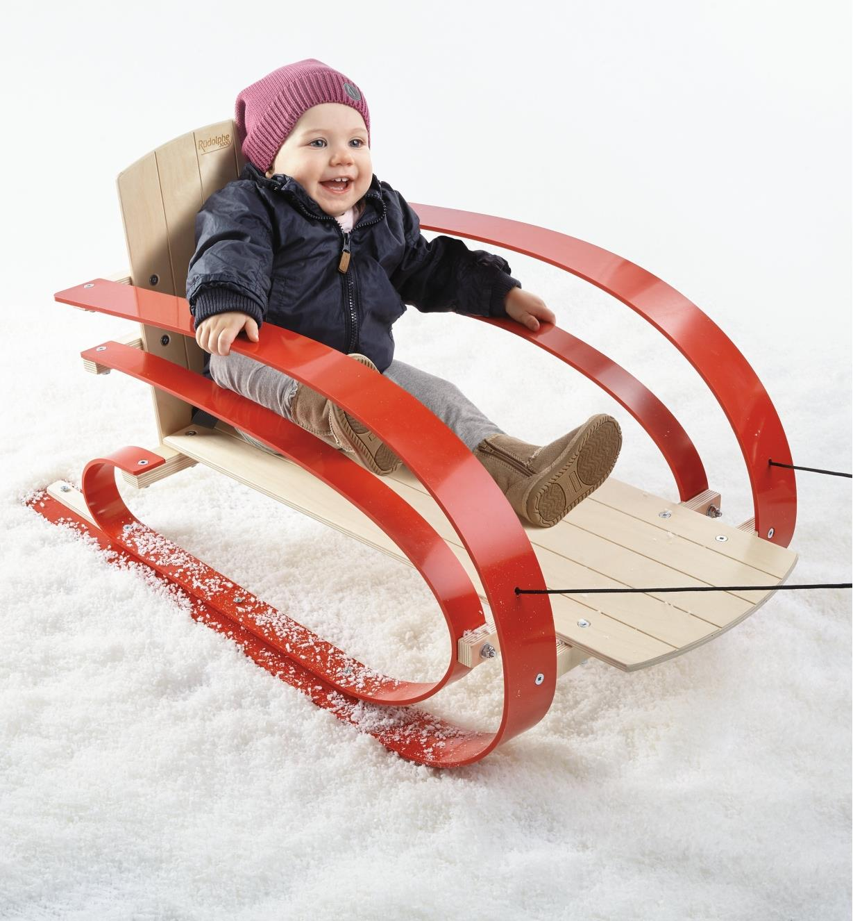 Suspension Sled holding a toddler is pulled over snow by the tow rope