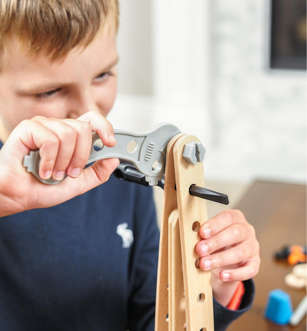 A boy uses the wrench to tighten a bolt while building a rocket