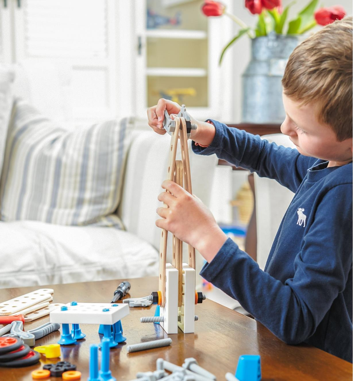 A boy building a rocket with the Brio Builder Construction Set