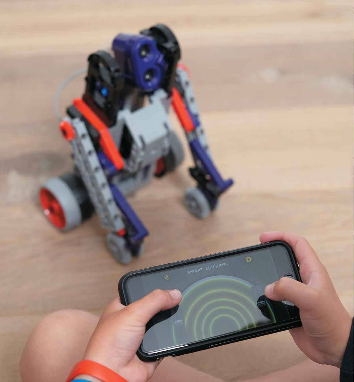 Un enfant commande le robot à distance à l'aide d'un téléphone intelligent.