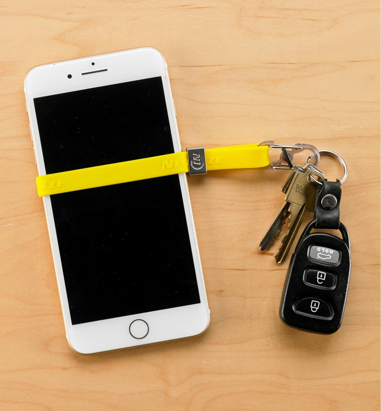 Cinch-A-Lot Stretch Strap wrapped around a cell phone and attached to a keychain