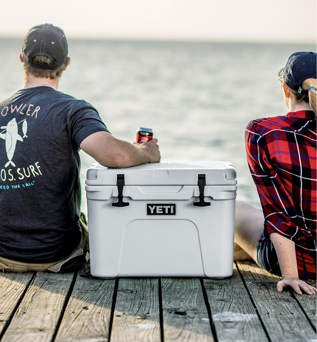 A man and woman sitting on a dock with a Yeti cooler between them