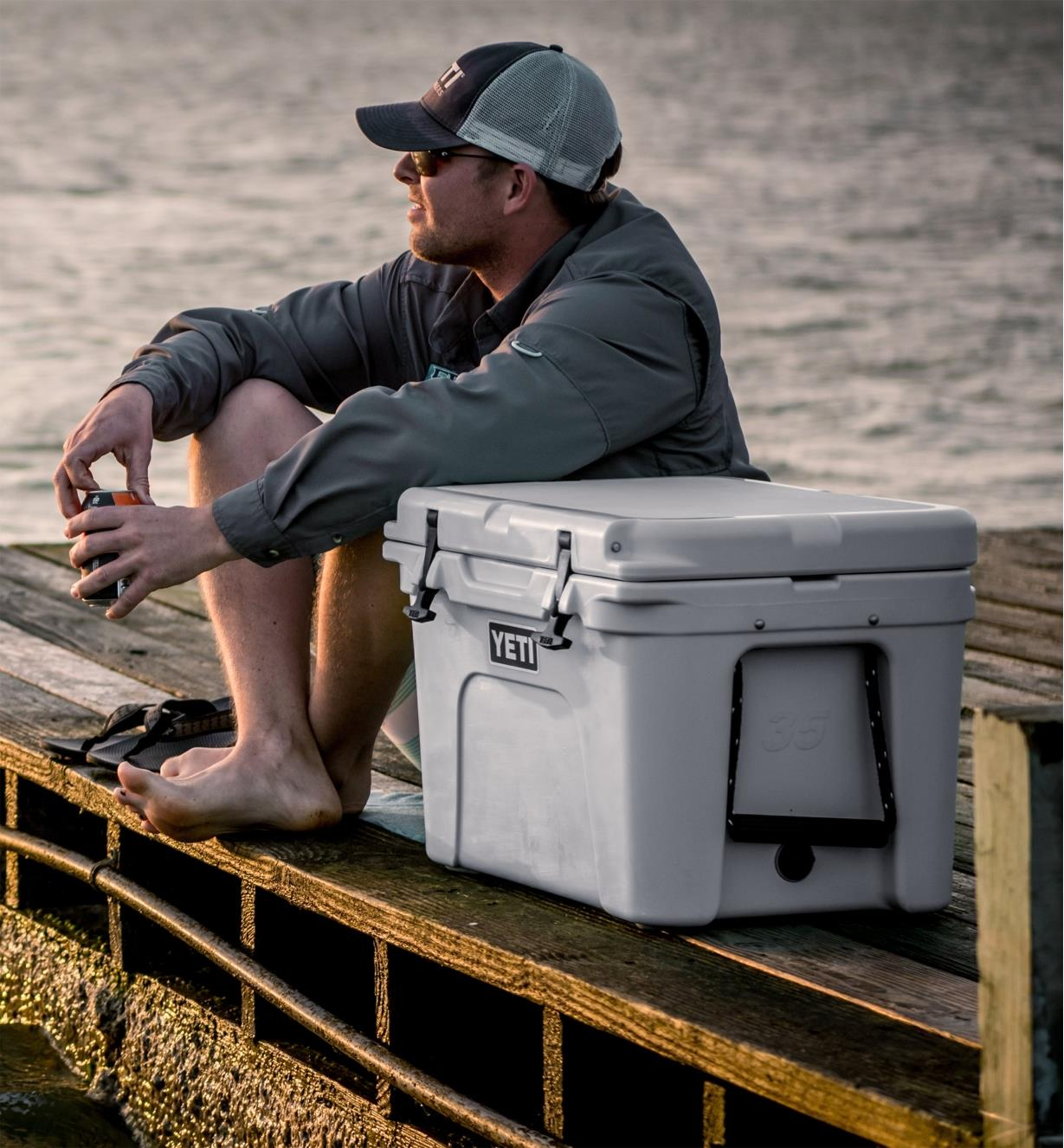 A man sitting on a dock beside a Yeti cooler