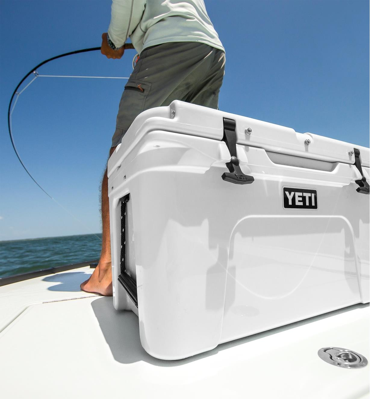 A Yeti cooler sits on boat deck with a man fishing in the background