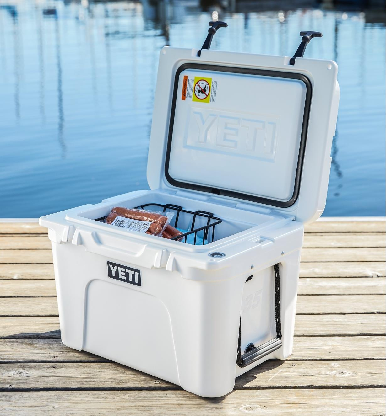 Yeti Tundra Hard-Sided 35 Cooler sitting on a dock with the lid open and food inside