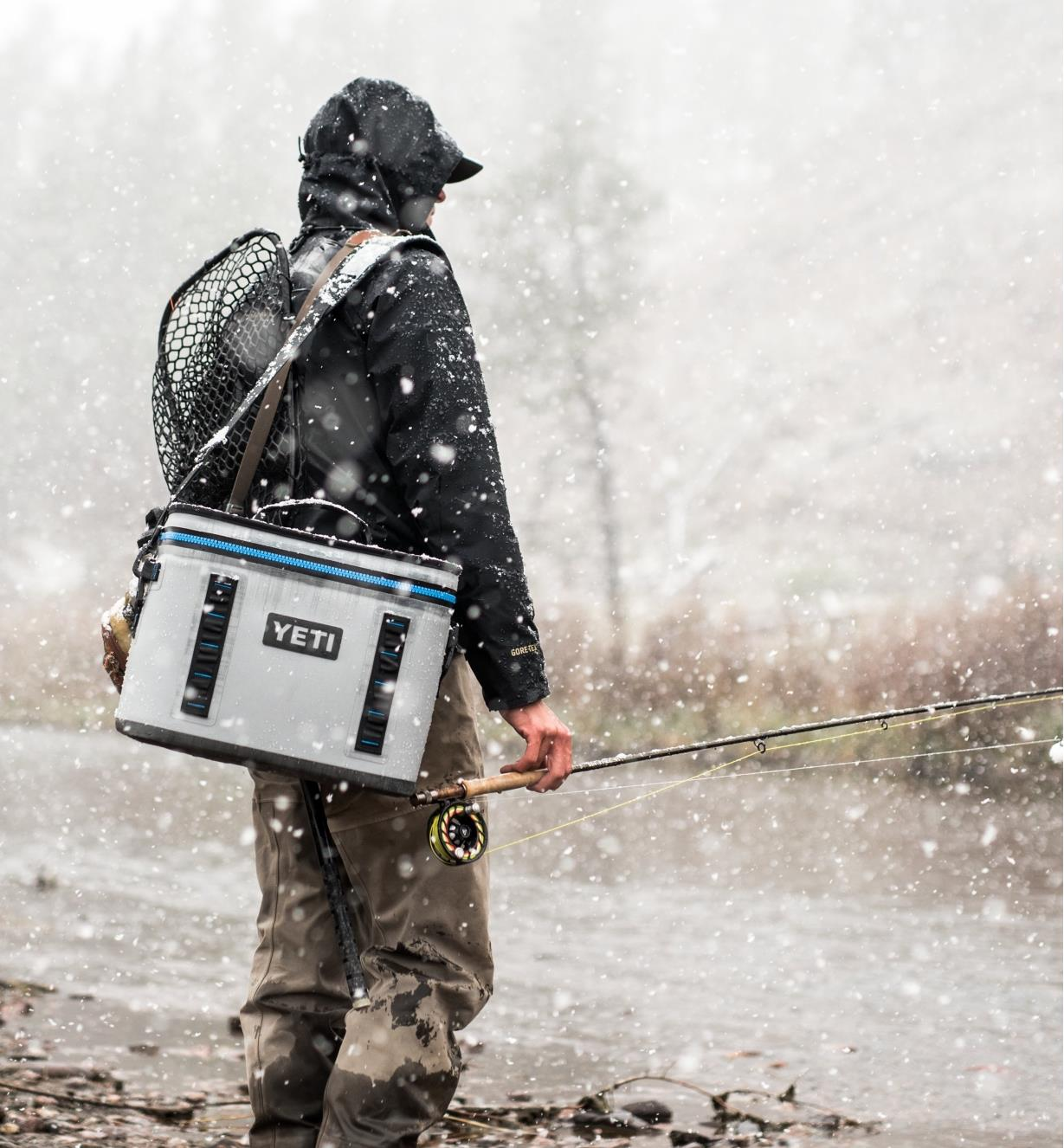 A man carrying a Yeti soft-sided cooler by the shoulder strap while fishing in a snowy location