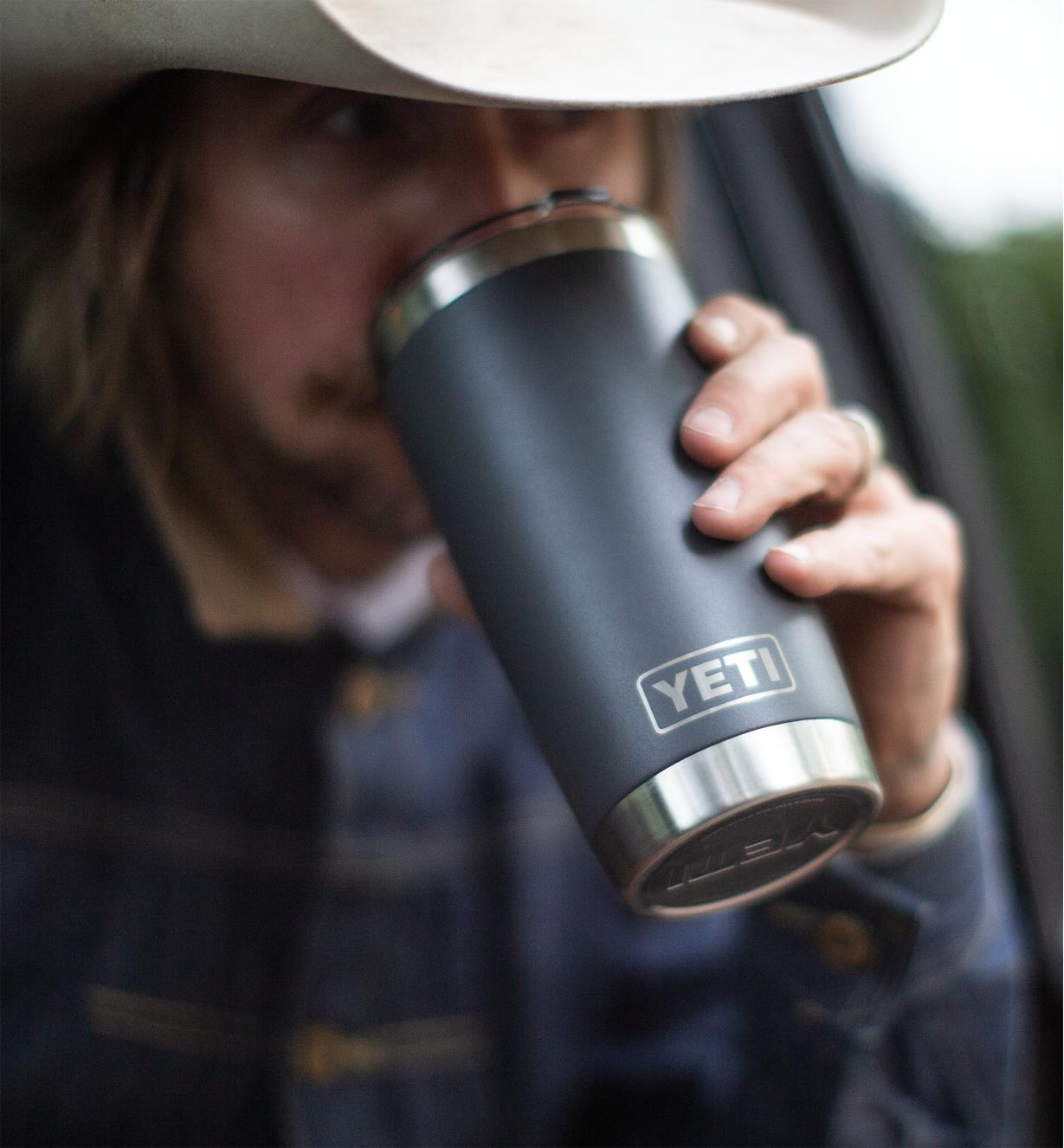 A man drinking from the 20 oz black Yeti Tumbler