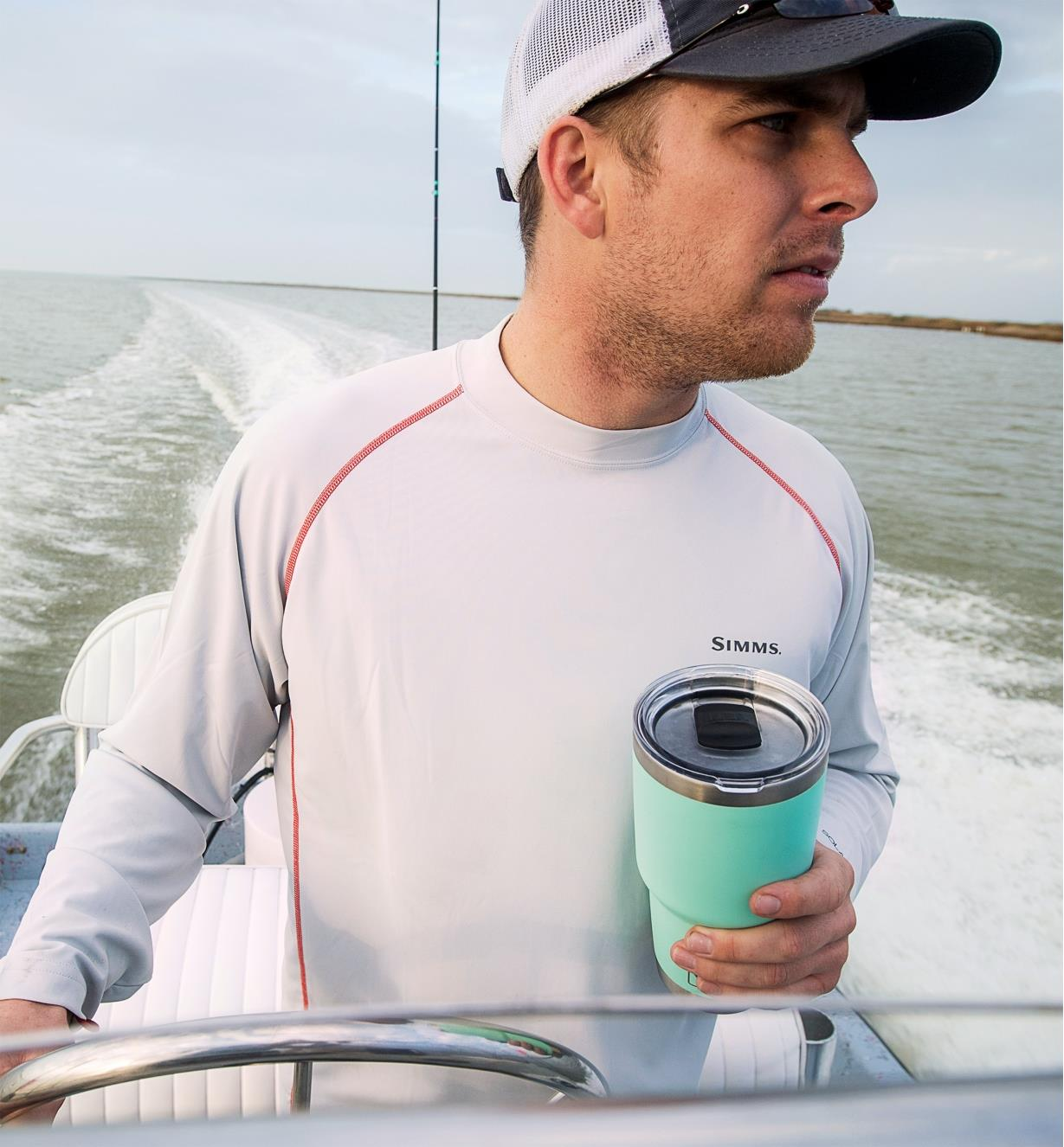 A man steering a boat holds a 30 oz seafoam Yeti Tumbler