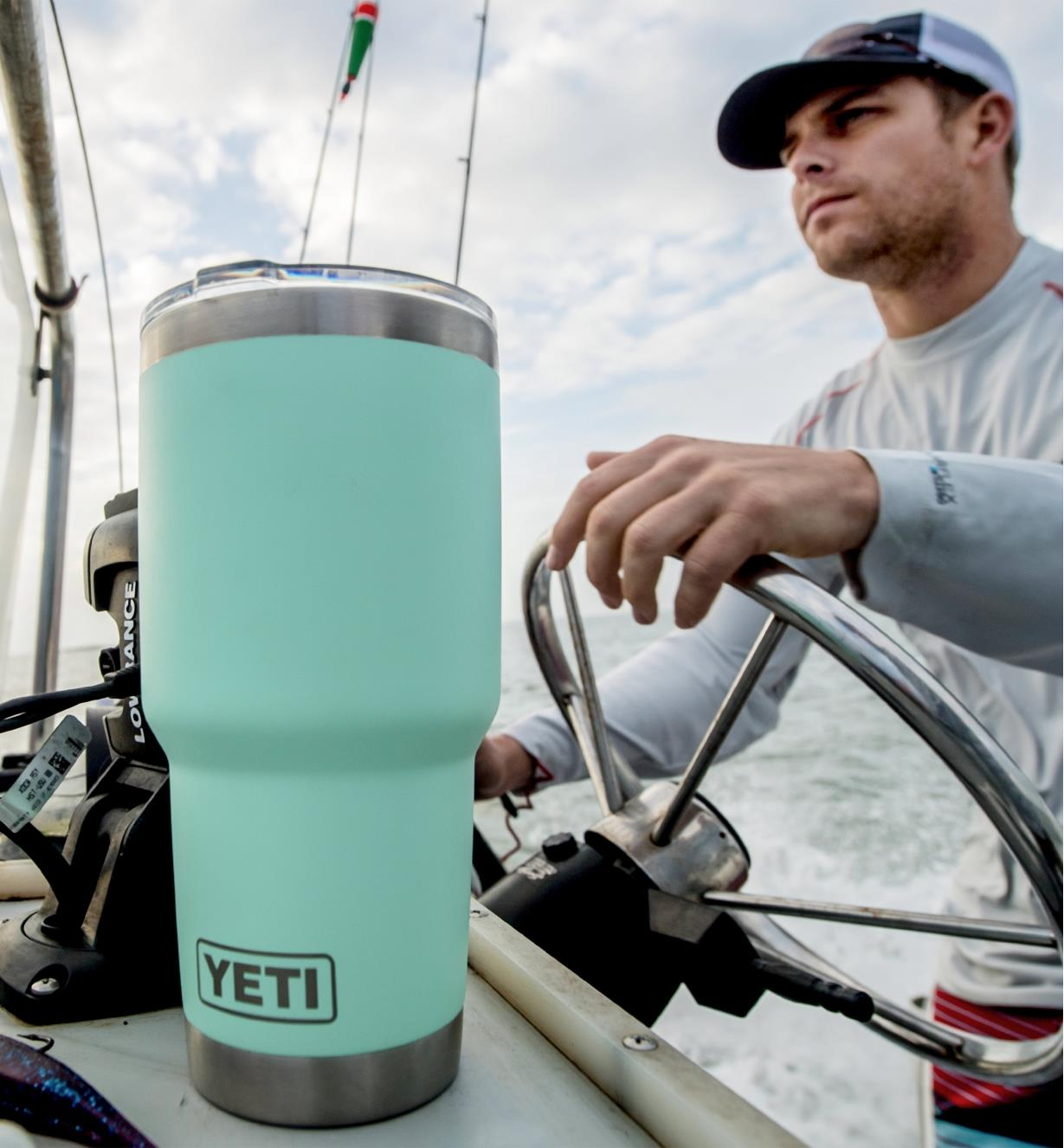 30 oz seafoam Yeti Tumbler on a boat with a man at the wheel in the background