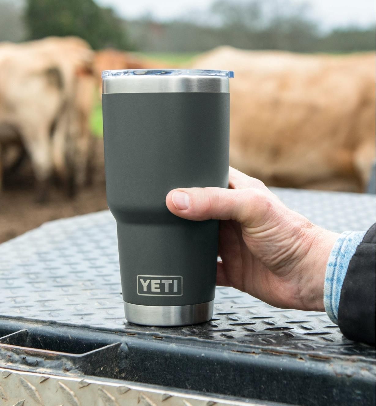 A man holds a 30 oz black Yeti Tumbler on an outdoor table