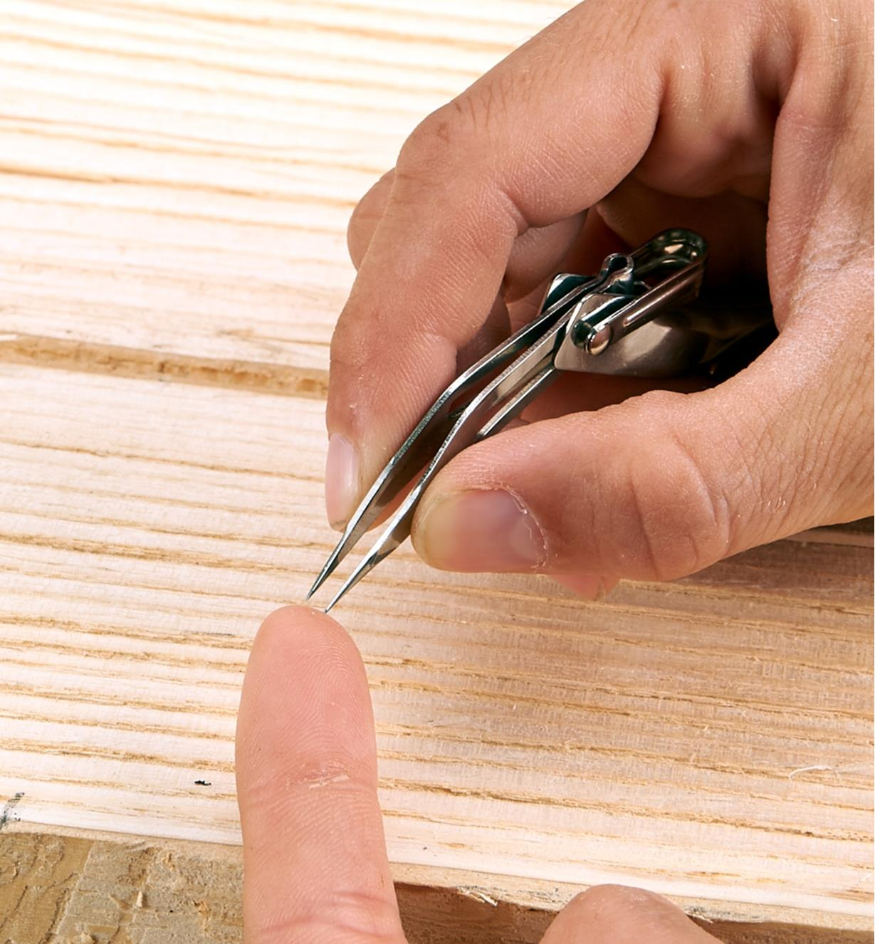 Removing a sliver from a finger with Fold-Out Tweezers