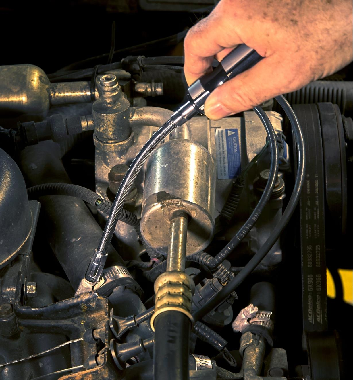 A person uses the flex-shaft nut driver to tighten a hose clamp in a truck's engine compartment