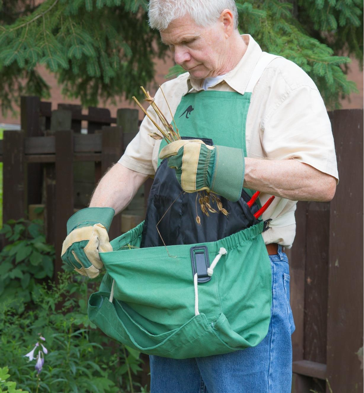 A man wearing the kangaroo pocket apron collects garden waste in the pocket