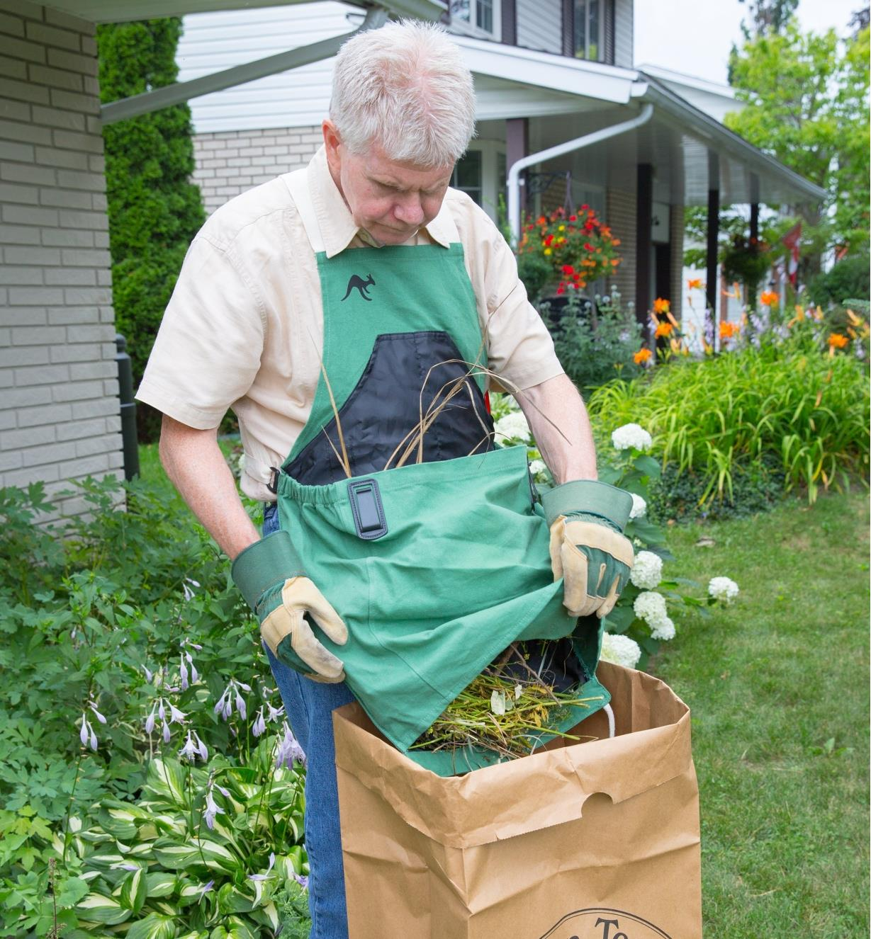 A man wearing the kangaroo pocket apron dumps garden waste from the pocket into a paper bag