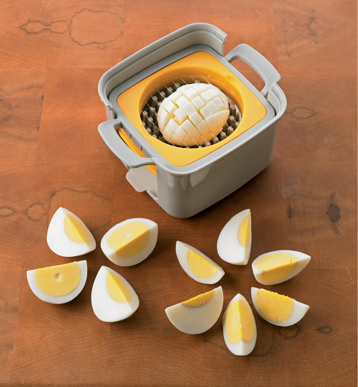 Egg Cutter slicing an egg, sitting next to eggs that have been cut into four and six sections