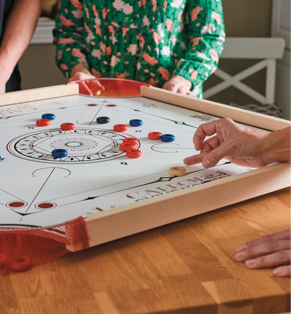 A player flicks the striker disc in a game of carrom