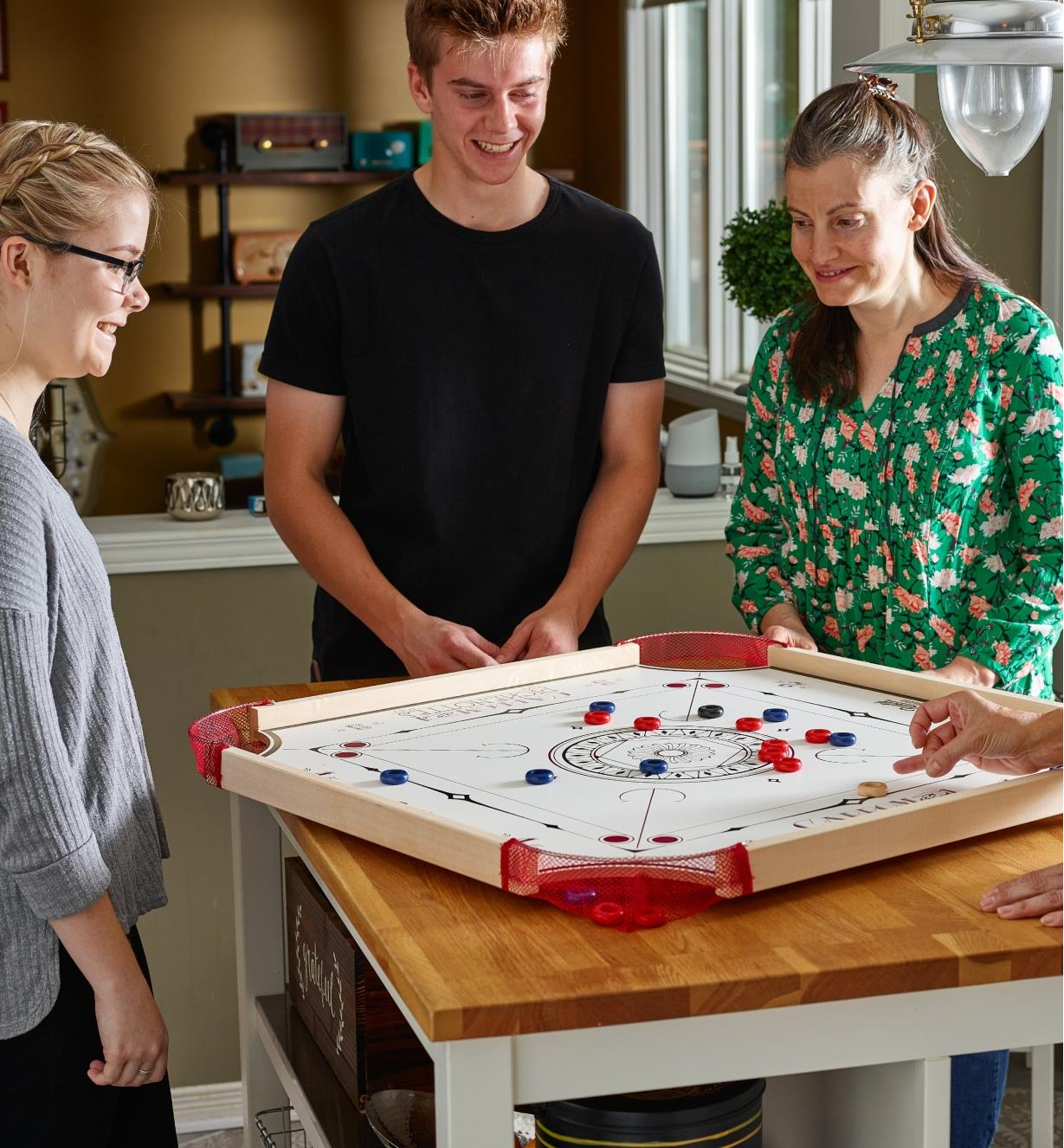 Four people playing carrom