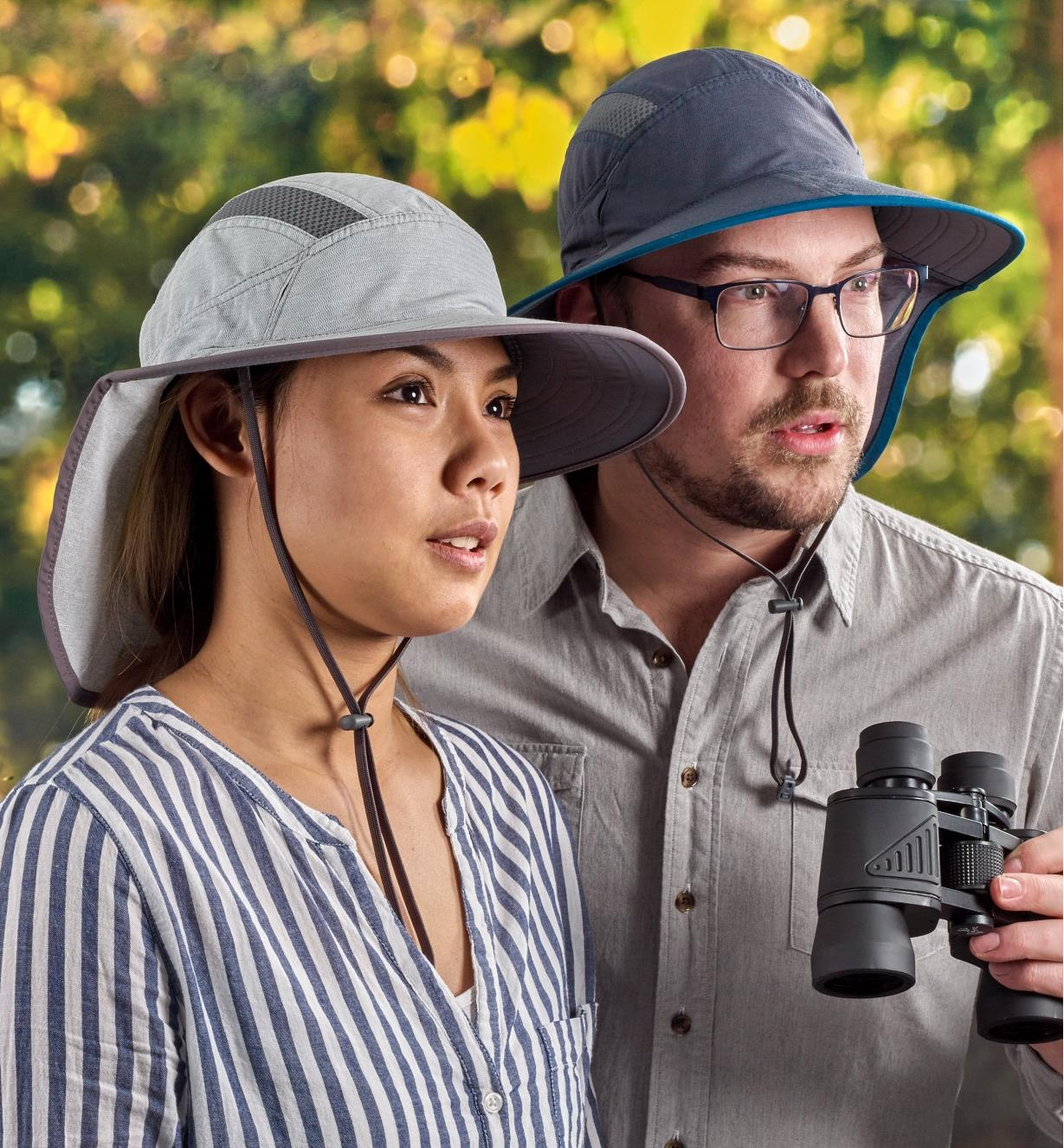 A woman and man wearing adventure sun hats while birdwatching
