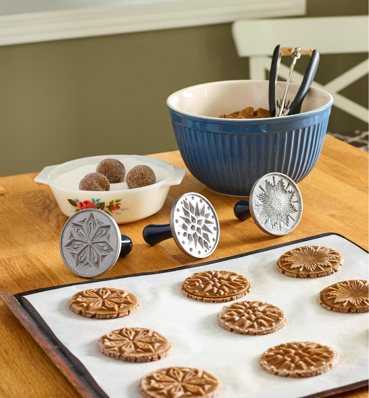 Set of three cookie stamps sitting on a counter next to a tray of cookies that have been stamped