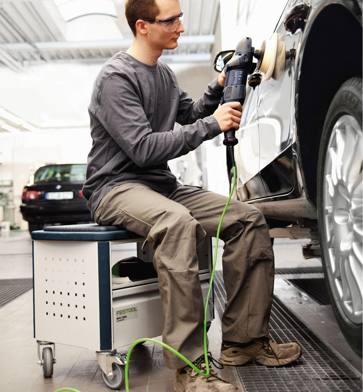 Man sitting on the MMFH 1000 multifunction stool while buffing a car