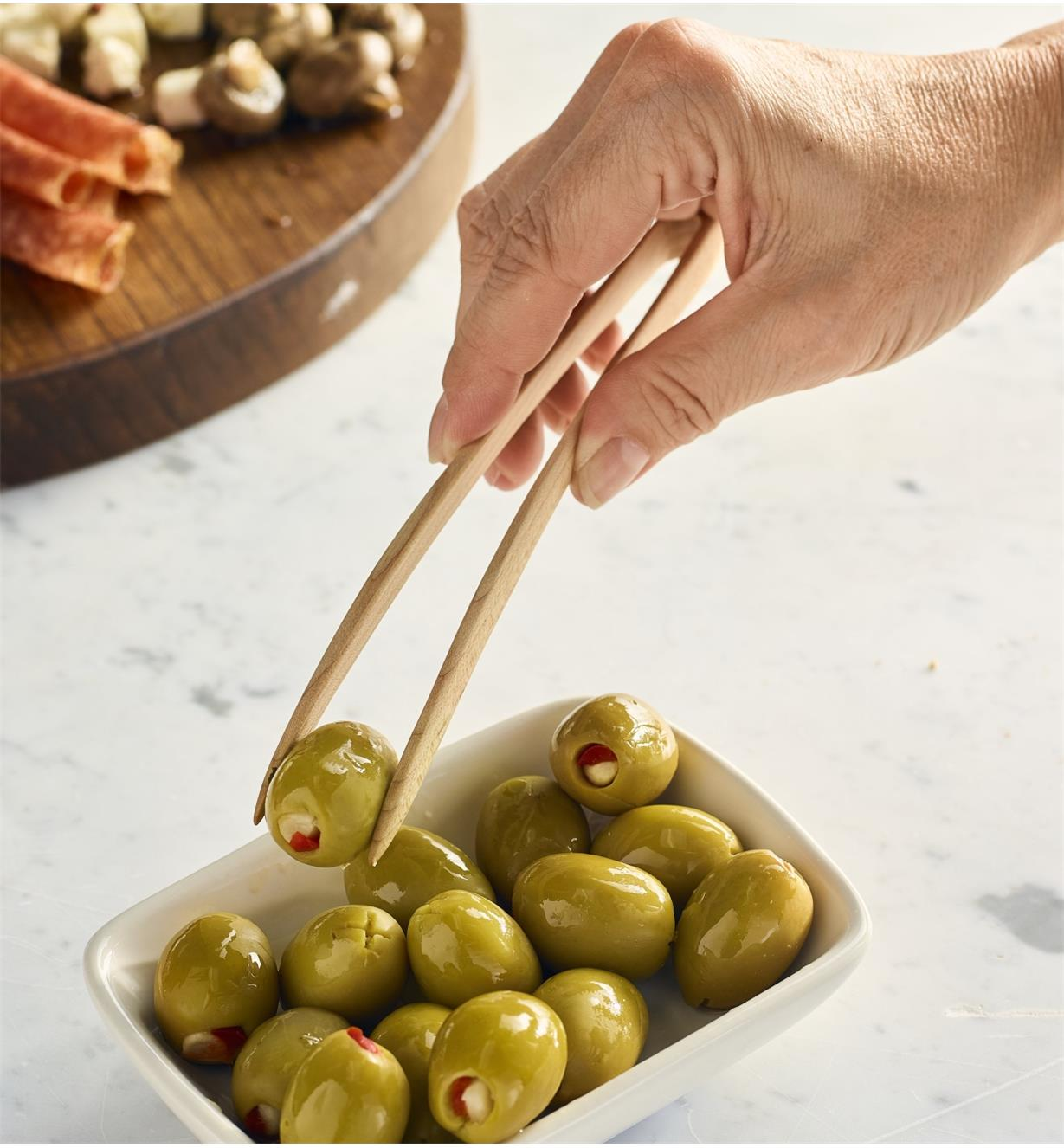Picking up olives with the small tongs