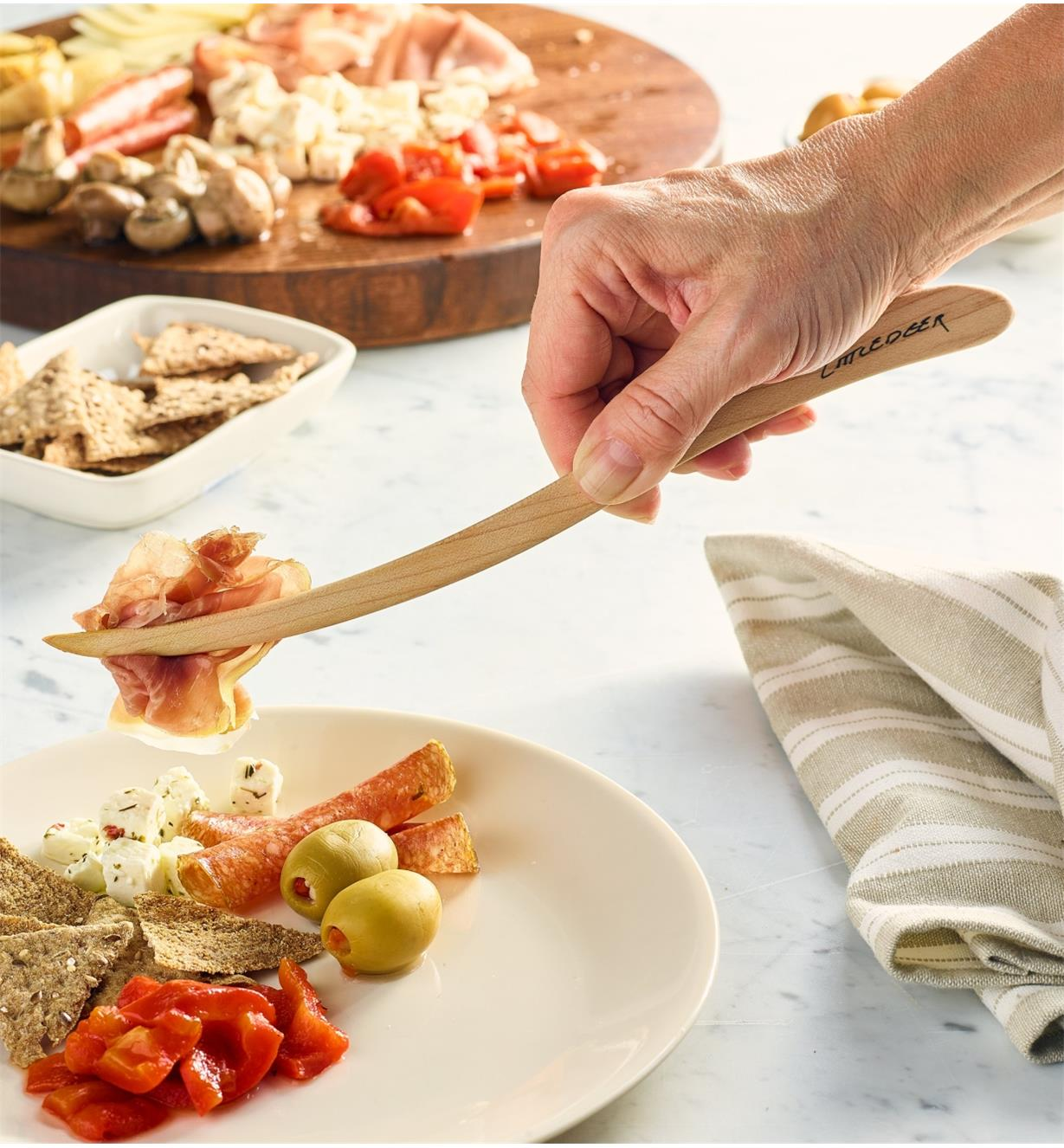 Transferring sliced meat from a charcuterie platter to a plate with the large tongs
