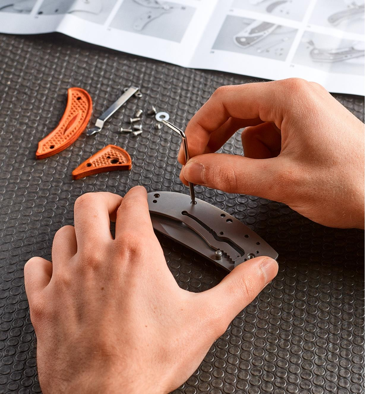 Personne assemblant les composants du couteau à platine-verrou
